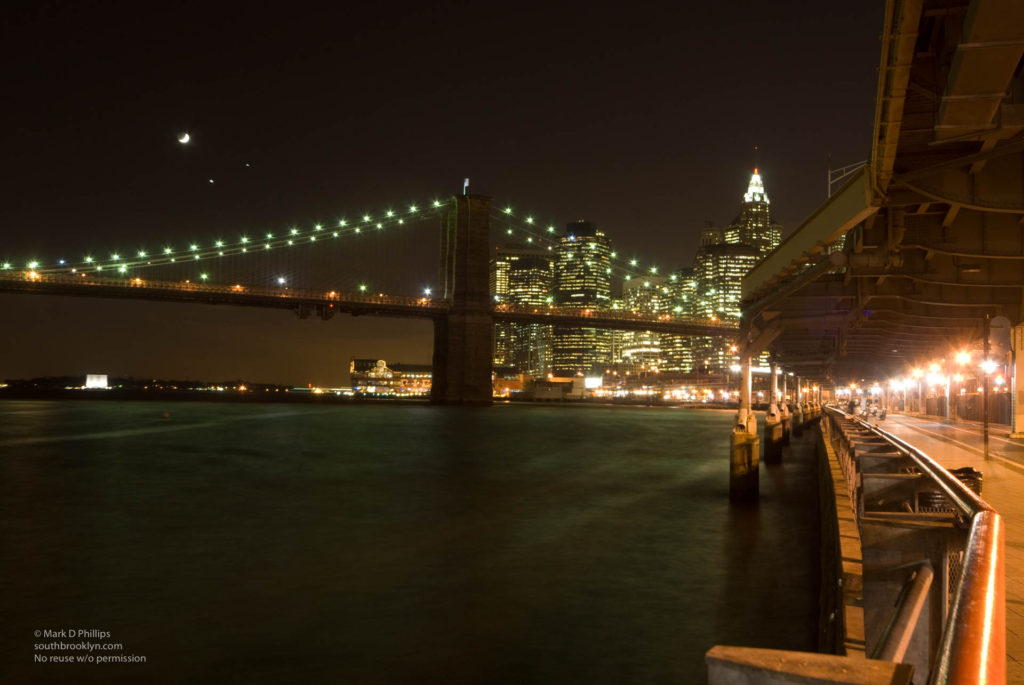 Crescent Moon, Jupiter, and Venus create a celestial triangle over the Brooklyn Bridge and New York Harbor on December 1, 2008. ©Mark D Phillips